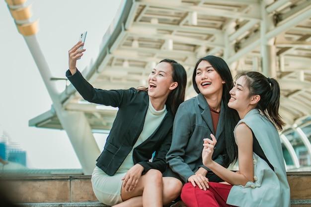 Zakenvrouw vrienden selfie met smartphone en wijzend op scherm verrast