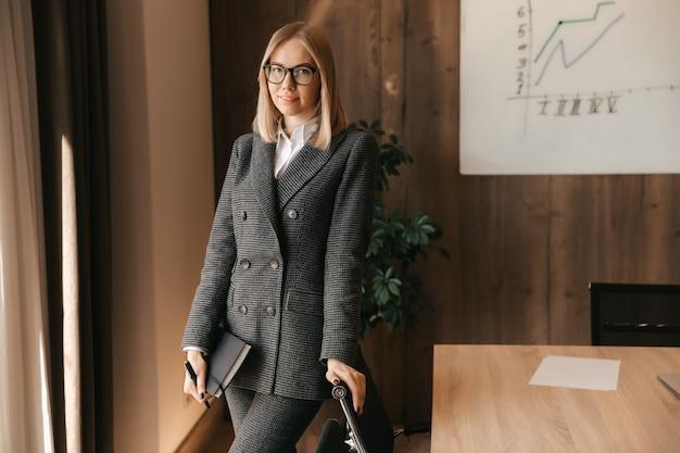 Zakenvrouw vrouw in haar kantoor staat met documenten en een pen in haar handen kantoormedewerker een vrouw in een klassiek pak