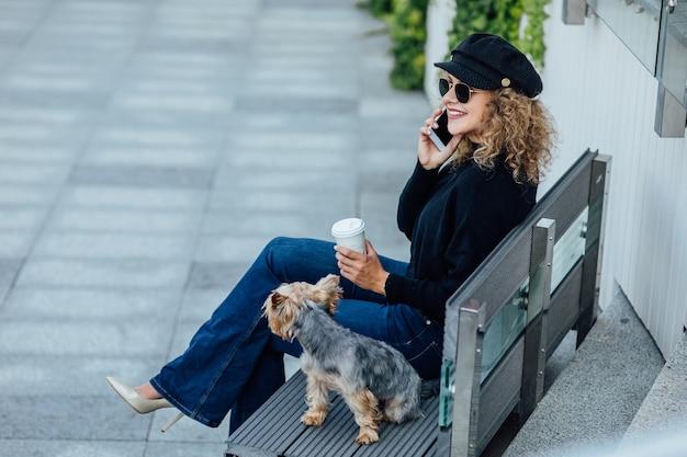 Zakenvrouw wandelen langs europese straat met kleine chihuahua rashond van twee kleuren aangelijnd bewolkt warm herfst lenteweer meisje gekleed in zwart shirt en naakt schoenen