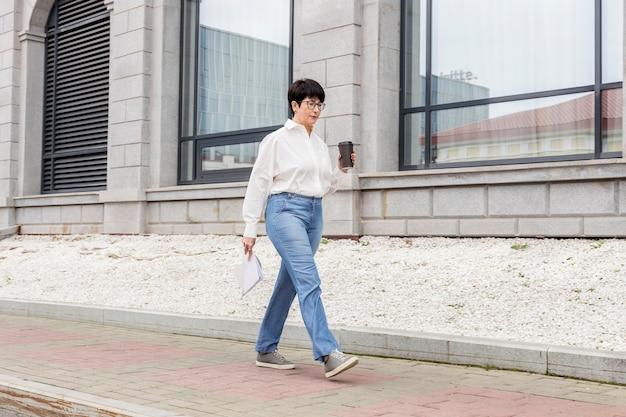 Zakenvrouw wandelen met een kopje koffie in haar hand