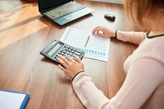 Zakenvrouw werken aan de tafel met behulp van een rekenmachine om getallen te berekenen.