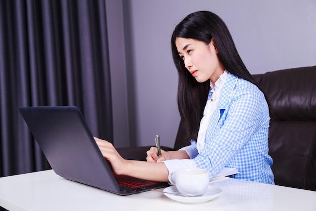 Zakenvrouw werken met laptop en schrijft een dagboek op de notebook
