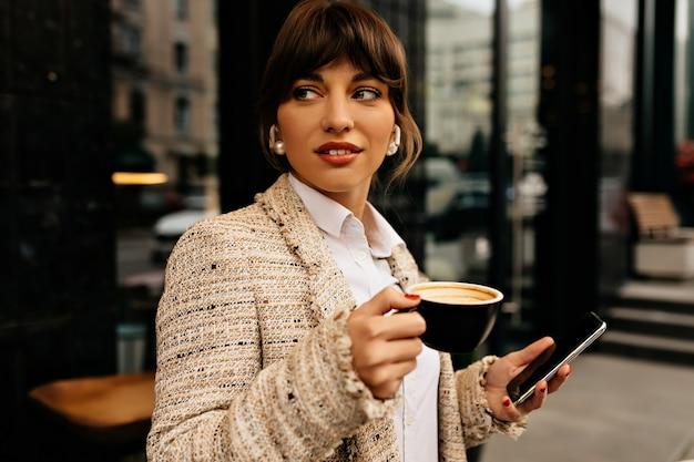 Zakenvrouw werken met smartphone terwijl het drinken van koffie buiten op de achtergrond van de stad hoge kwaliteit foto