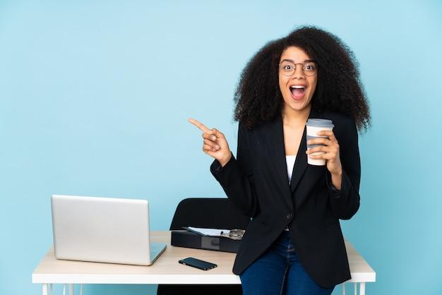 Zakenvrouw werken op haar werkplek verrast en wijzende vinger naar de zijkant
