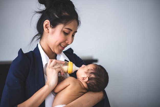 Zakenvrouw werken vanuit huis, baby meisje te houden
