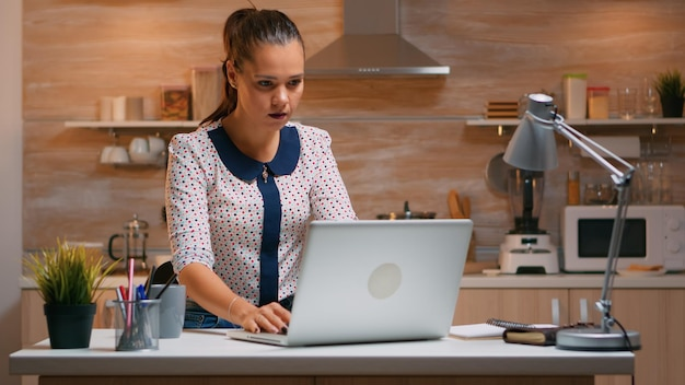 Zakenvrouw werken vanuit huis zittend in de keuken 's avonds laat op laptop te typen. drukke, gefocuste werknemer die moderne technologienetwerken gebruikt om overuren te maken voor lezen, schrijven, zoeken