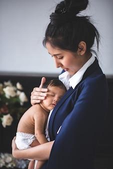 Zakenvrouw werkt door haar baby te houden