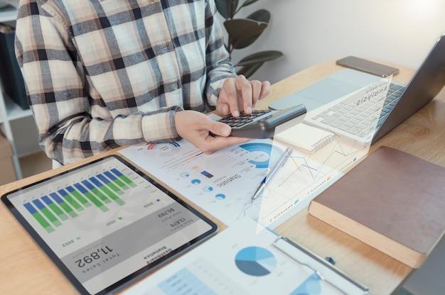 Zakenvrouw werkzaam in financiën en boekhouding analyseer het financiële grafiekbudget met rekenmachine op kantoor aan huis.