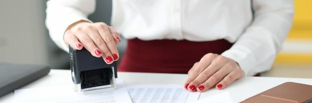 Zakenvrouw zet een stempel op documenten op werktafeldiensten van notarissen en notariskantoren