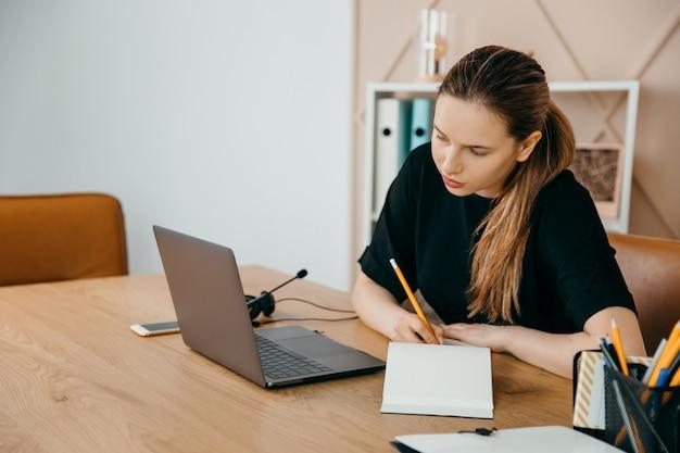 Zakenvrouw zit aan bureau en kijkt naar laptop die thuis aantekeningen maakt