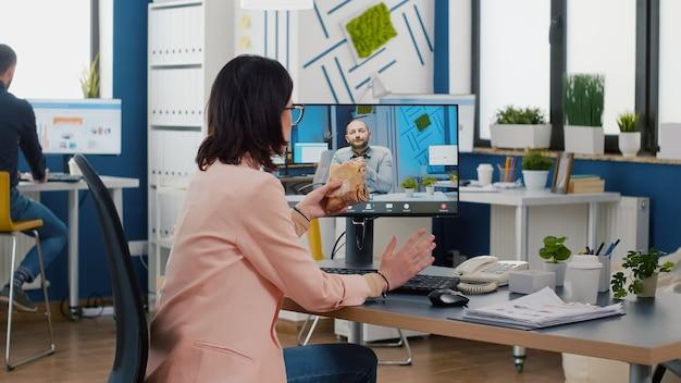 Zakenvrouw zit aan de balie in het kantoor van het bedrijf en eet een broodje tijdens een online videogesprekconferentie