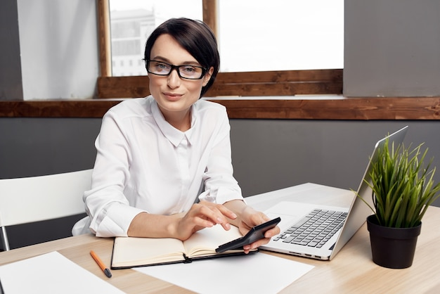 Zakenvrouw zit aan haar bureau voor laptop secretaresse professional