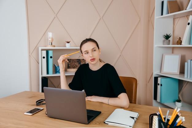 Zakenvrouw zit aan het bureau en kijkt naar laptop die aantekeningen maakt en thuis denkt