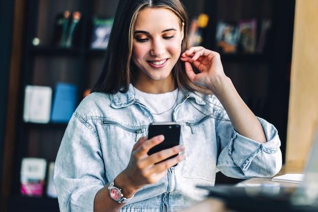Zakenvrouw zit aan tafel, houdt smartphone in haar handen, schrijft berichten, voert zakelijke correspondentie.