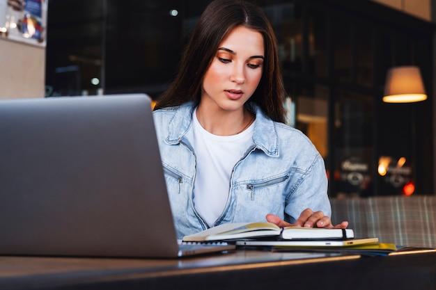 Zakenvrouw zit aan tafel in café voor laptop, leest notities uit notitieblok, maakt notities in dagboek.