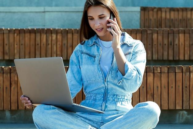 Zakenvrouw zit op bankje in openbaar park, werkt op laptop. aantrekkelijk donkerbruin meisje gekleed in denim