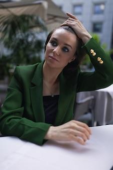 Zakenvrouw zitten in café en wat rust na alle vergaderingen en interviews. groen stijlvol jasje en zwarte blouse, kort kapsel, naaktmake-up.