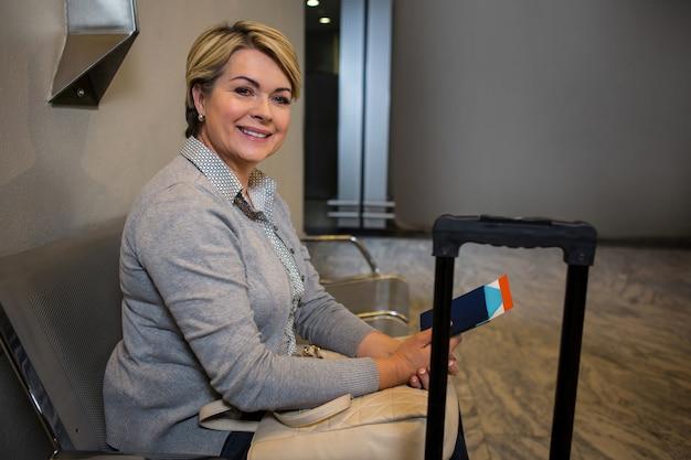 Zakenvrouw zitten met bagage en paspoort vn wachtruimte