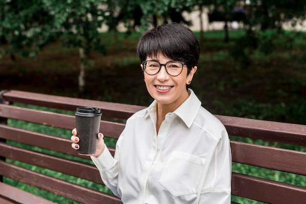 Zakenvrouw zittend op een bankje en een kopje koffie drinken
