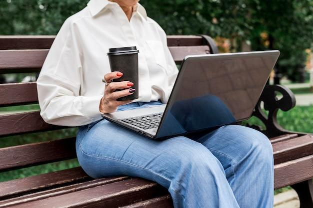 Zakenvrouw zittend op een bankje met laptop