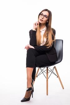 Zakenvrouw zittend op een zwarte stoel op wit