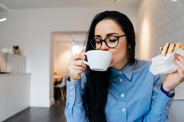 Zakenvrouw zittend op kantoor aan tafel en koffie drinken