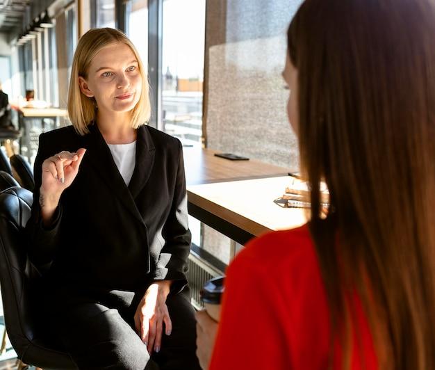 Zakenvrouwen die op het werk gebarentaal gebruiken om met elkaar te communiceren