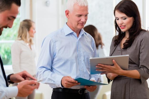 Zakenvrouwen en -mannen die in bureau presentatie in een standup vergadering bekijken