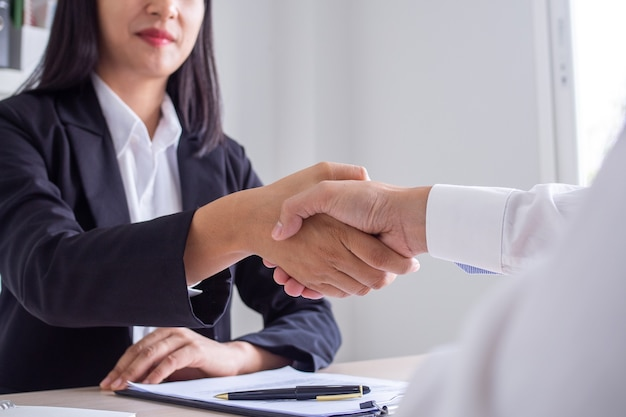 Zakenvrouwen en werkzoekenden schudden elkaar de hand nadat ze ermee hebben ingestemd een baan te aanvaarden en deze als werknemer in het bedrijf goed te keuren. of een joint venture-overeenkomst tussen de twee zakenlieden