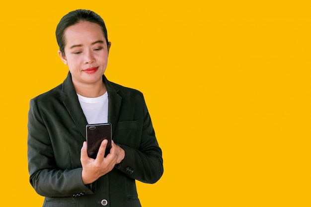 Zakenvrouwen gebruiken smartphones om videogesprekken te voeren op een gele achtergrond