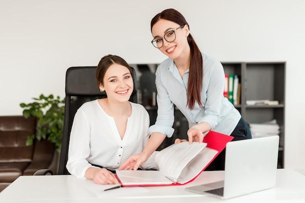 Zakenvrouwen op kantoor glimlachen en reviseren van documenten op de werkplek