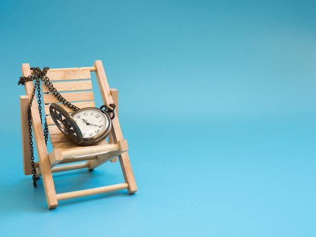 Zakhorloge op de houten ligstoel op blauwe achtergrond