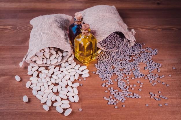 Zakken bonen en linzen en een fles olijfolie op een houten tafel