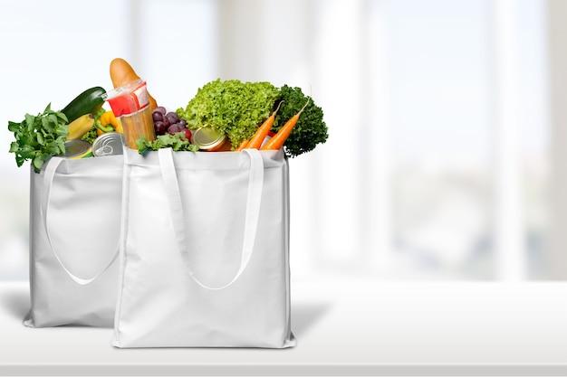 Zakken met brood en diverse groenten op lichte achtergrond