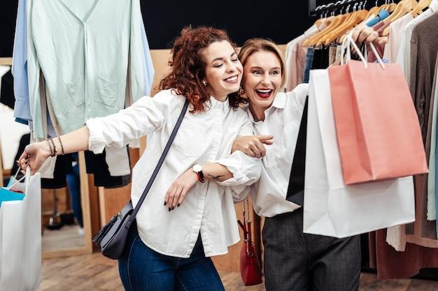 Zakken met kleding. vrolijke moeder en dochter glimlachen terwijl ze de winkel verlaten met zakken nieuwe kleren