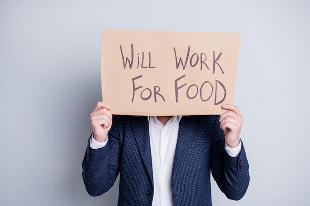 Zal werken voor eten. foto van werknemer man lijdt slachtoffer financiële crisis verloren werk houd plakkaat zoeken werk voedsel uitwisseling verbergen gezichtsuitdrukking draag blauw pak geïsoleerde grijze achtergrond