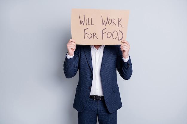Zal werken voor eten. foto van werknemer ontslagen man lijdt slachtoffer financiële crisis verloren werk houd plakkaat zoeken werk voedsel uitwisseling verberg gezichtsuitdrukking draag blauw pak geïsoleerde grijze achtergrond