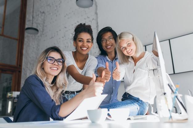 Zalig afrikaans vrouwelijk hoofd van de marketingafdeling poseren met duim omhoog na hard werken