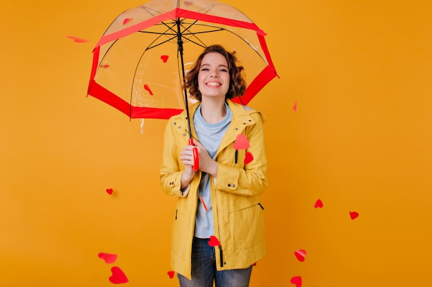 Zalig bleek meisje in stijlvol jasje staande onder parasol met oprechte glimlach. jonge vrouw in elegante herfstkleding poseren op gele muur.