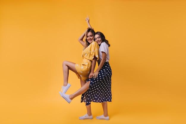 Zalig brunette meisje in lange rok poseren met haar zus. indoor portret van spectaculaire vriendinnen geïsoleerd op geel.
