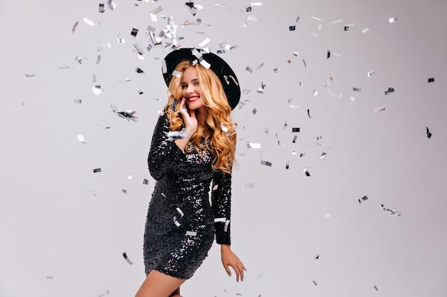 Zalig charmant meisje in zwarte outfit die zich onder confetti bevindt. portret van verfijnde elegante vrouw in jurk en hoed.
