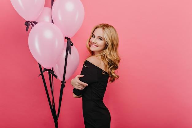 Zalig feestvarken dat over schouder met opgewekte glimlach kijkt. witte sensuele vrouw lachen in zwarte jurk vakantie vieren.