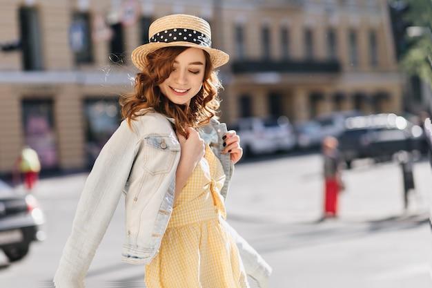 Zalig gembermeisje dat in gele kleding door de stad loopt. openluchtportret van blije kaukasische dame in strohoed die op straat glimlachen.