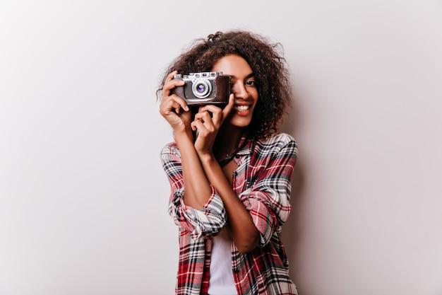 Zalig glimlachend meisje dat met camera schoten maakt. indoor shot van vrouwelijke shotgraaf draagt geruit overhemd.