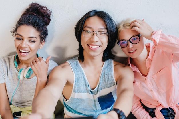 Zalig krullend afrikaans meisje met grote koptelefoon tijd doorbrengen met haar vrienden op de universiteit. charmante blonde vrouwelijke student poseren met glimlach terwijl haar aziatische collega selfie maken.