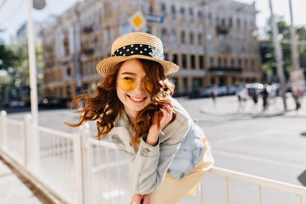 Zalig krullend meisje in schattige hoed chillen op straat. buiten foto van vrij vrouwelijk model met rood haar lachen in zomerdag.
