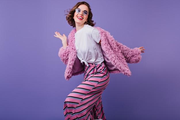 Zalig krullend meisje in zonnebril lachen terwijl poseren in roze bontjasje. binnen schot van schattige jonge vrouw dansen op paarse muur met glimlach.