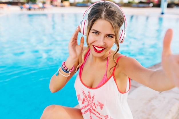 Zalig krullend meisje met felle lippenstift selfie maken tijdens rust in openluchtzwembad in zonnige dag