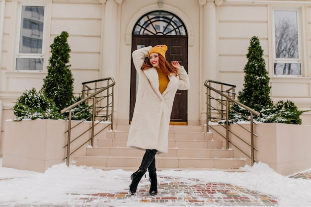 Zalig meisje in witte jas positieve emoties uitdrukken in de winter. buiten schot van mooie blanke vrouw poseren in januari.