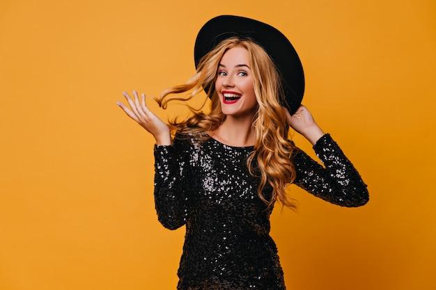 Zalig meisje in zwarte jurk spelen met haar lange haren. indoor foto van enthousiaste blanke vrouw draagt een hoed.